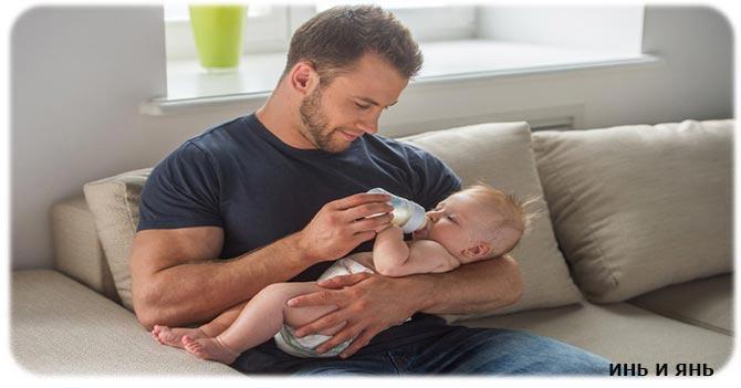 Мужчина кормит малыша